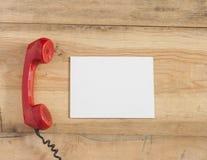 Rode ouderwetse telefoonontvanger op houten lijst Stock Afbeeldingen