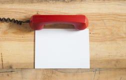 Rode ouderwetse telefoonontvanger op houten lijst Stock Fotografie
