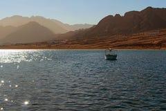 Rode Overzees in een kalm weer Boot dichtbij kust in het overzees wordt vastgelegd die Strand met sommige gebouwen, zand Hooggebe royalty-vrije stock foto's