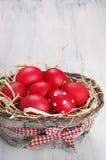 Rode Paaseieren in mand Royalty-vrije Stock Afbeeldingen