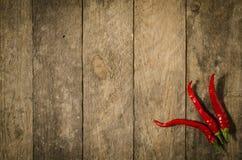 Rode paprika over houten lijst Stock Afbeeldingen