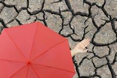 Rode paraplu en een hand die van de mens zich op gebarsten aarde bevinden en han Royalty-vrije Stock Foto