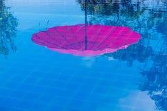 Rode paraplubezinning in pool Royalty-vrije Stock Afbeeldingen