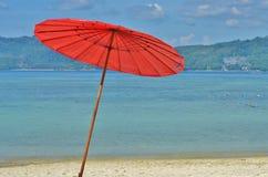 Rode parasol op het strand tegen het overzees Royalty-vrije Stock Fotografie