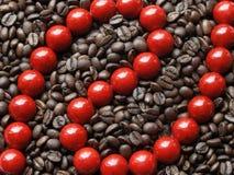 Rode parels in bruine bonen Royalty-vrije Stock Fotografie