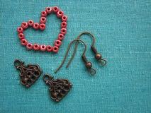 Rode parels in vorm die van hart, oorringen, met de hand gemaakte juwelen maken Royalty-vrije Stock Afbeeldingen