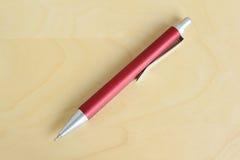 Rode pen op houten lijst Stock Fotografie