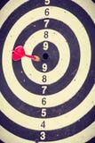 Rode pijltjepijl die in het dartboard raken Stock Foto's