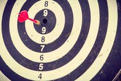 Rode pijltjepijl die in het dartboard raken Stock Afbeelding