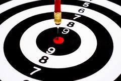 Rode pijltjepijl die in het doelcentrum raken van dartboard Stock Foto
