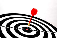 Rode pijltjepijl die in het doelcentrum raken van dartboard Royalty-vrije Stock Afbeelding