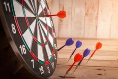 Rode pijltjepijl die in het doelcentrum raken van dartboard Stock Afbeeldingen
