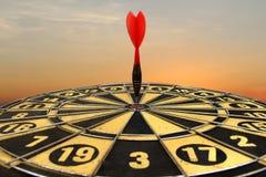 Rode pijltjepijl die in het doelcentrum raken van dartboard Royalty-vrije Stock Foto