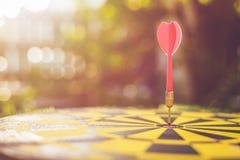 Rode pijltjepijl in het centrum van dartboard Onduidelijk beeld en bokeh in zon Royalty-vrije Stock Afbeelding