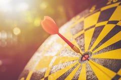Rode pijltjepijl in het centrum van dartboard Onduidelijk beeld en bokeh in zon Royalty-vrije Stock Fotografie