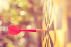 Rode pijltjepijl in het centrum van dartboard Onduidelijk beeld en bokeh in zon Royalty-vrije Stock Foto