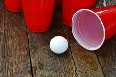 Rode Plastic het Drinken Koppen en Gemorst Bier Stock Afbeeldingen