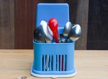 Rode plastic lepel en roestvrije lepels in blauwe plastic opslag Royalty-vrije Stock Afbeelding