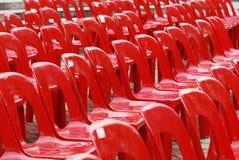 Rode Plastic Stoelen Stock Afbeeldingen