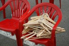 Rode plastic stoelen met lege houten hangers voor kleren royalty-vrije stock fotografie