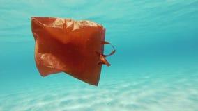 Rode plastic zak oceaanverontreiniging stock video