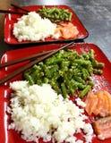 Rode platen met gezond Aziatisch voedsel: witte rijst, rode vissenzalm en slabonen in sesam op donkere grijze lijst Royalty-vrije Stock Foto