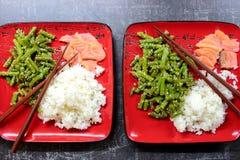 Rode platen met gezond Aziatisch voedsel: witte rijst, rode vissenzalm en slabonen in sesam op donkere grijze lijst Stock Foto's