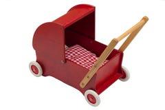 Rode poppenkinderwagen met pop Stock Foto's