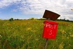 Rode postpostbus op een gebied Stock Fotografie