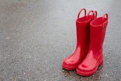 Rode regenlaarzen op natte bestrating Stock Foto