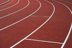 Rode renbaan en witte stegen op sportstadion royalty-vrije stock afbeeldingen