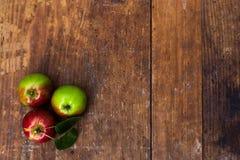 Rode rijpe appelen bij donkere houten lijst Royalty-vrije Stock Fotografie