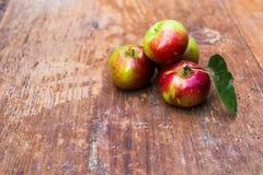 Rode rijpe appelen bij donkere houten lijst Stock Foto's