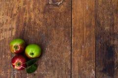 Rode rijpe appelen bij donkere houten lijst Royalty-vrije Stock Foto's