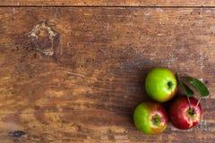 Rode rijpe appelen bij donkere houten lijst Stock Fotografie