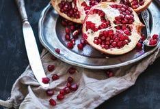 Rode rijpe gepelde granaatappel op rustieke metaalplaat Royalty-vrije Stock Afbeelding