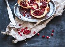 Rode rijpe gepelde granaatappel op rustieke metaalplaat Stock Foto's