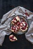 Rode rijpe gepelde granaatappel op rustieke metaalplaat en beige keukenhanddoek Royalty-vrije Stock Afbeeldingen