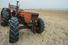 Rode roestige tractor op strand Stock Foto
