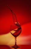 Rode Rose Wine Tempting Abstract Splashing op gradiëntachtergrond van de gele en rode kleuren op de weerspiegelende oppervlakte Royalty-vrije Stock Afbeelding