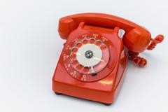 Rode roterende ouderwetse telefoon op witte achtergrond stock foto's