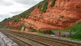 Rode rots en spoorweg in Dawlish-Konijnenveld, Devon stock afbeelding