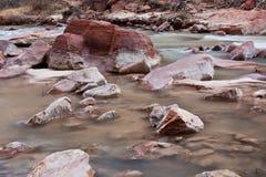 Rode rotsen op een rivierbed stock fotografie