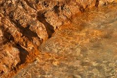 Rode rotsen op oever Stock Foto