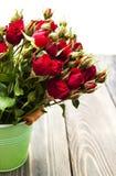 Rode rozen in emmer Royalty-vrije Stock Afbeeldingen