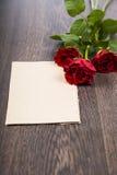 Rode rozen en kaart op een donkere houten achtergrond Stock Foto's