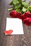 Rode rozen en kaart op een donkere houten achtergrond Stock Afbeelding