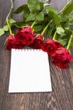 Rode rozen en kaart op een donkere houten achtergrond Royalty-vrije Stock Afbeeldingen