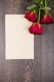 Rode rozen en kaart op een donkere houten achtergrond Royalty-vrije Stock Foto