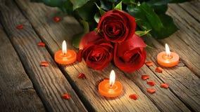 Rode rozen en romantische kaarsen op oude houten lijst, de dag van Valentine ` s stock videobeelden